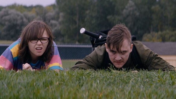 Simon (Kyle Gallner) and Patty (Emily Skeggs) lying in the grass, observing something.