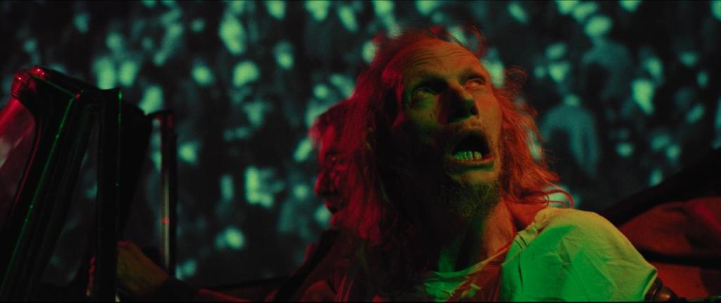 Barry (Gary Green) in acar, watching his psychedelic surroundings with his mouth open.