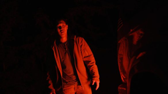 Aysen (Borislav Stepanov) standing in darkness, bathed in red light, his own distorted reflection next to him.