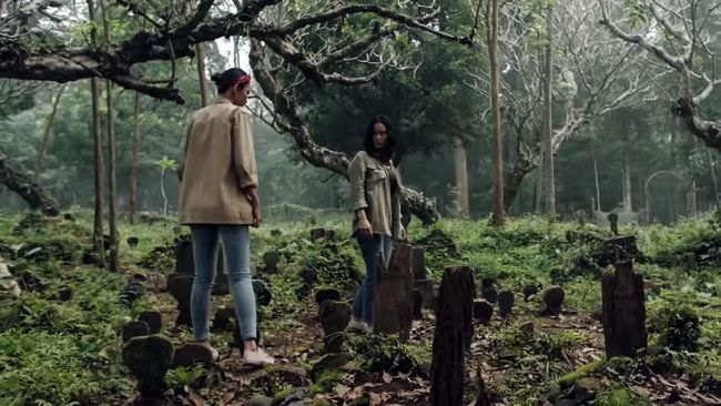 Dini (Marissa Anita) and Maya (Tara Basro) walking through a cemetery.