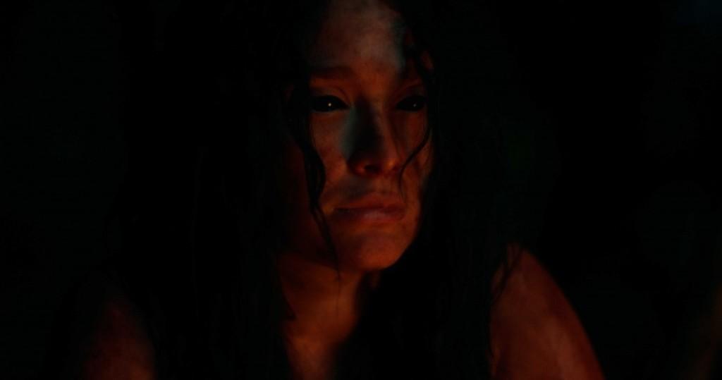 Kerana (Lali Gonzalez) with all-black eyes lit by campfire.
