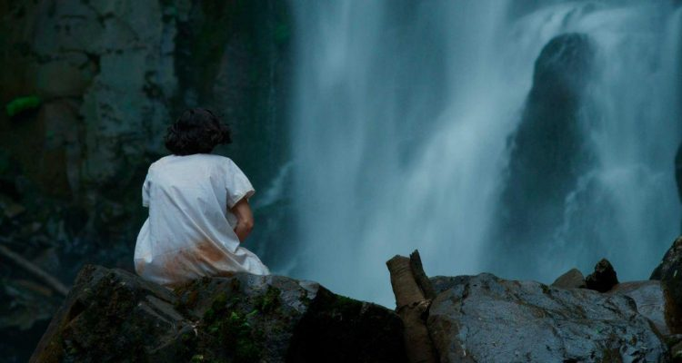 Julia (María Soldi) sitting at the foot of a waterfall with a bloody night-gown. We see her only from behind, cradling something.