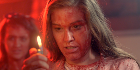 Daisy (Chelsey Grant) covered in blood, lighting a lighter.