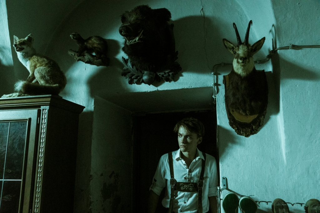 Hendrik ( Leon Orlandianyi) in a dark room filled with hunting trophies.