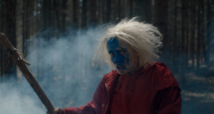 Eve (Lucie Debay) with wild hair, her face covered in blue color, holding up a branch as a weapon.