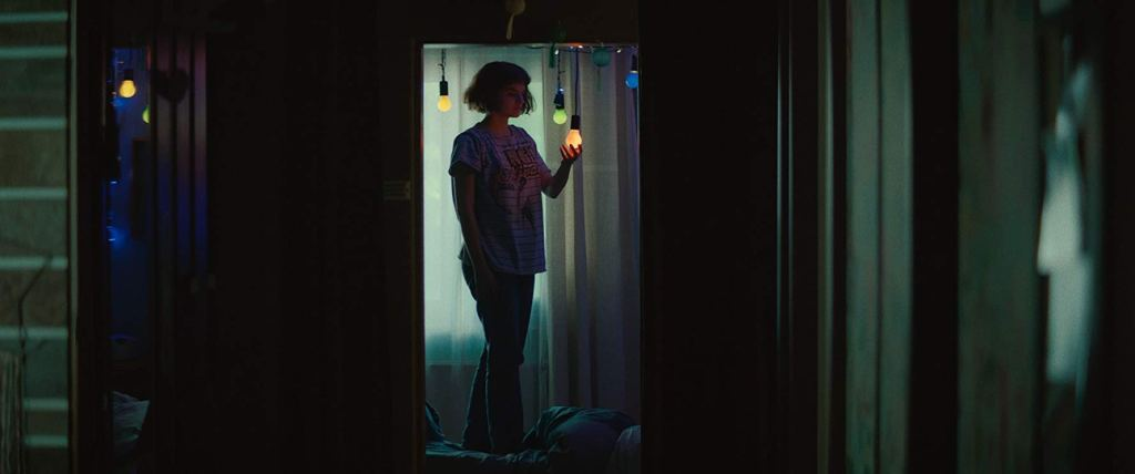 Jeanne (Noémie Merlant) standing in her room under colorful lightbulbs.