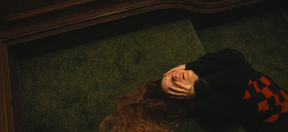 Maud (Morfydd Clark) lying on the stairs, covering her face with her hands.