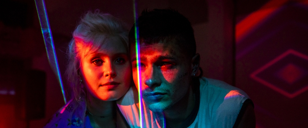 Milla (Eliza Scanlen) in a blond wig and Moses (Toby Wallace) with colorful lights on them.