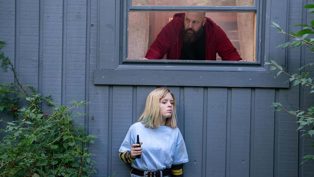 Becky (Lulu Wilson) standing under a window. Dominick (Kevin James) is looking out the window, hoping to find her.