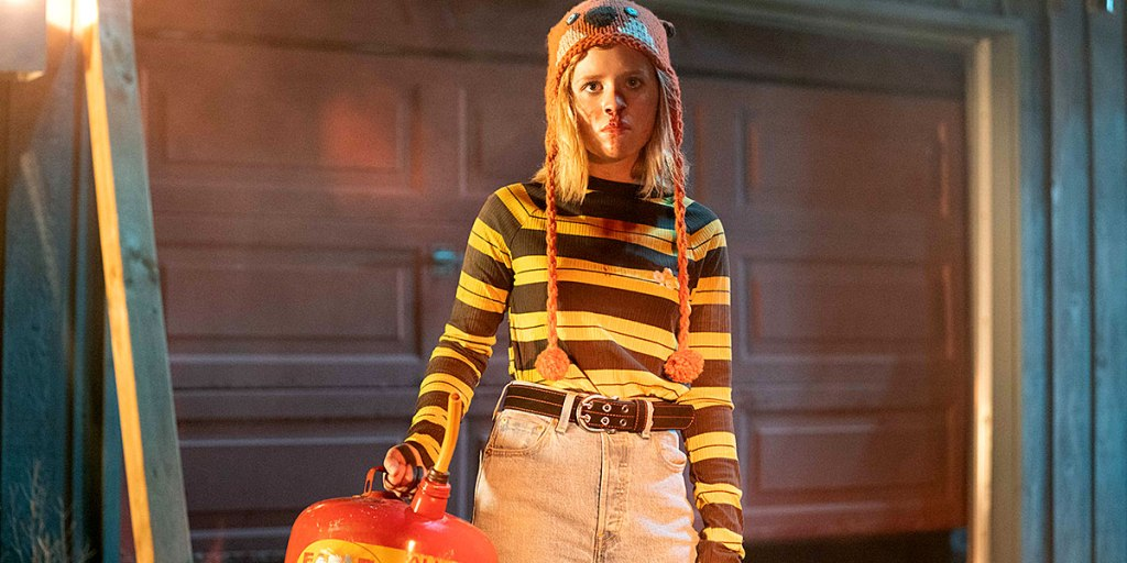 Becky (Lulu Wilson) witha  can of gas in front of a garage door.