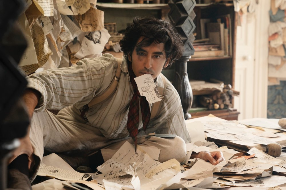 David (Dev Patel) lying in a pile of paper, one of the pieces in his mouth.