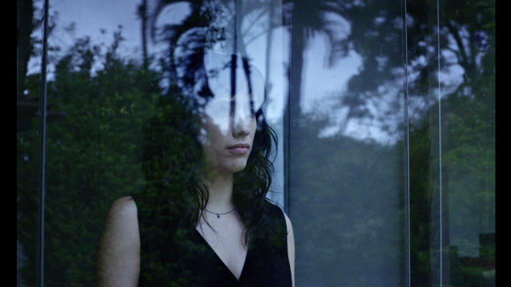 Laura (Clara Kinzo) looking out a window.