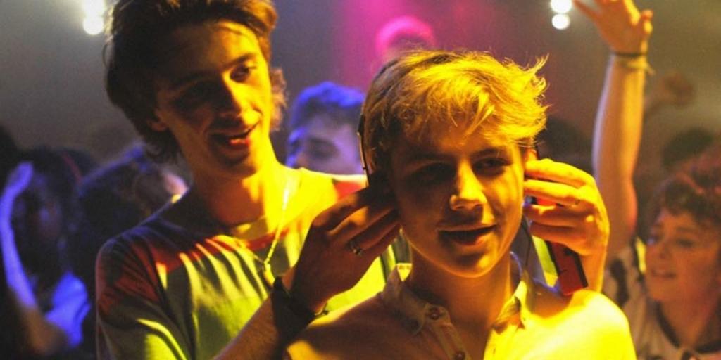 David (Benjamin Voisin) putting headphones on Alexis (Félix Lefebvre) in a club.
