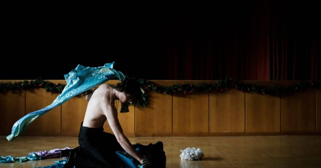 Mario (Thomas Prenn) tearing through a bag of clothes in his rehearsal space.