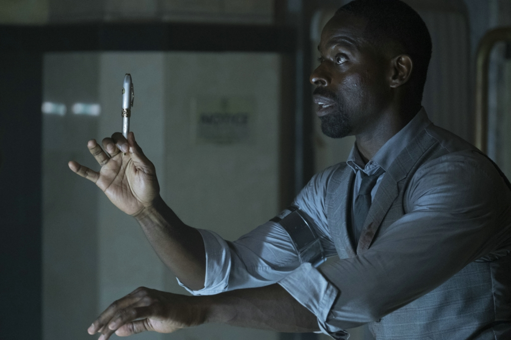 Waikiki (Sterling K. Brown) holding up a pen.