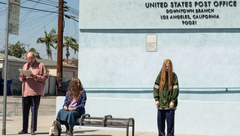 Old Dolio (Evan Rachel Wood) and her parents Robert (Richard Jenkins) and Theresa (Debra Winger) waiting in front of a post office.