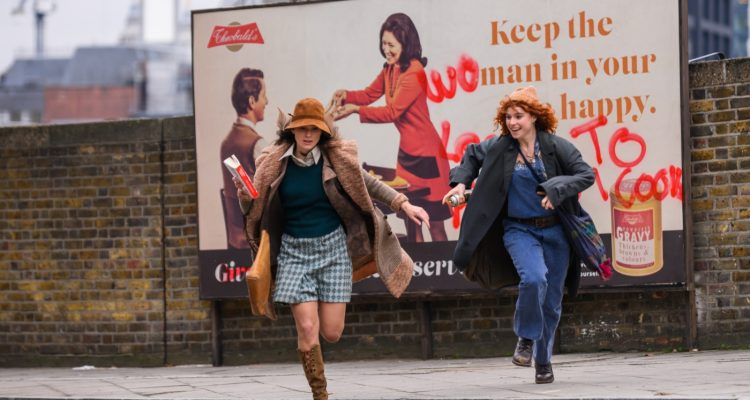 Sally Alexander (Keira Knightley) and Jo Robinson (Jessie Buckley) running from a billboard that Jo just spraypainted on.