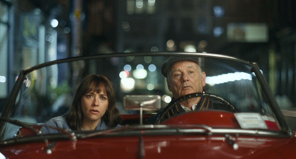 Laura (Rashida Jones) and Felix (Bill Murray) in a flashy sportscar, looking at something with suspicion.
