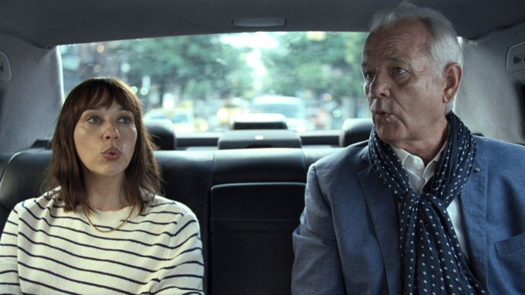 Laura (Rashida Jones) and Felix (Bill Murray) in the back of a car, both whistling.