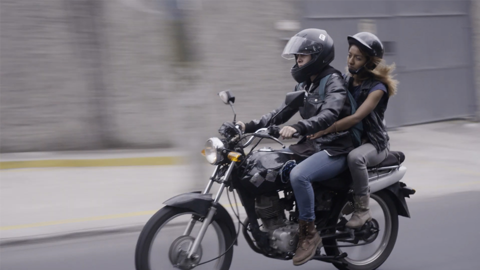 Claudia (Andrea Henry) and Mariá (Vanessa Hernández) zipping through the city on Claudia's motorbike.