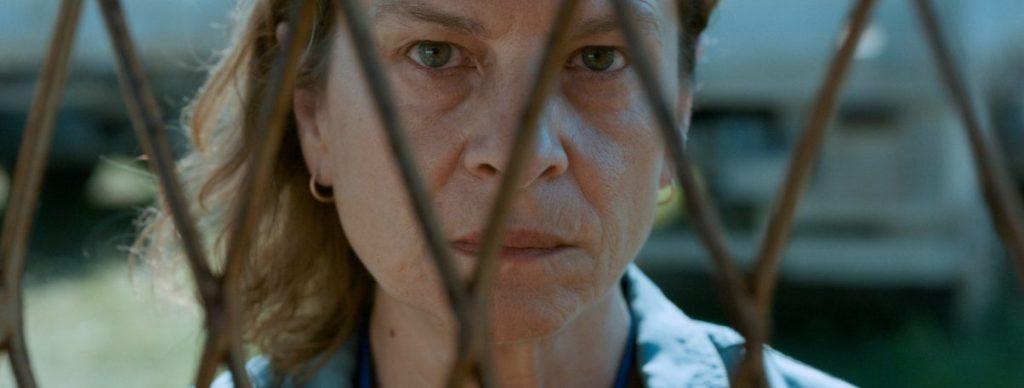 Aida (Jasna Djuricic) looking through a fence.