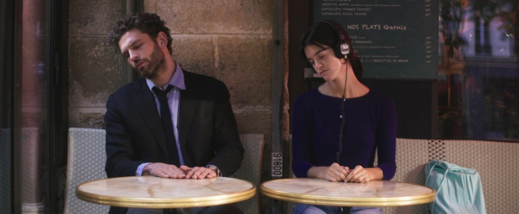 Suzanne (Suzanne Lindon) and Raphaël (Arnaud Valois) sitting next to each other in a cafe. She is wearing headphones and they are both in the same position - heads tilted, hands on the table.