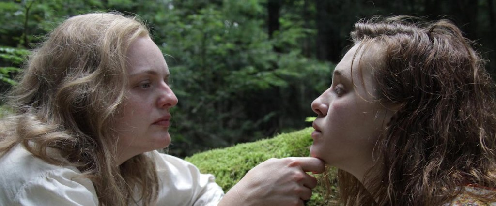 Shirley (Elisabeth Moss) and Rose (Odessa Young) in the forest. Shirley is grabbing Rose's chin.
