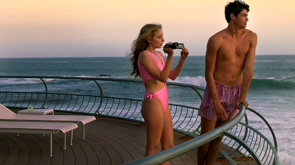 Penny (Carson Meyer) and Johnny (Noah Centineo) standing on a balcony over the sea.