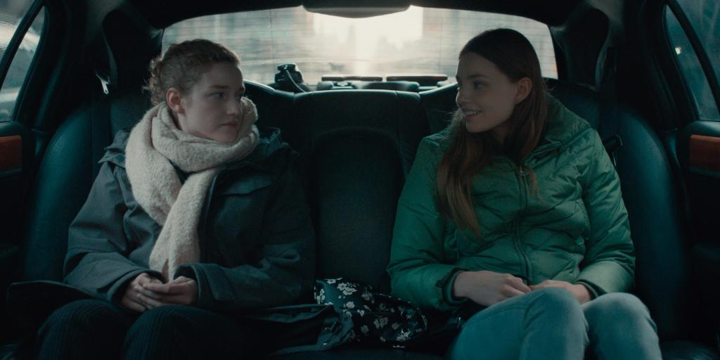 Jane (Julia Garner) driving with Sienna (Kristine Froseth) in the back of a fancy car.