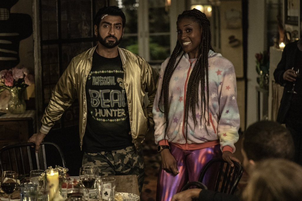 Leilani (Issa Rae) and Jibran (Kumail Nanjiani) dressed in strange clothes at their friends' dinner party.
