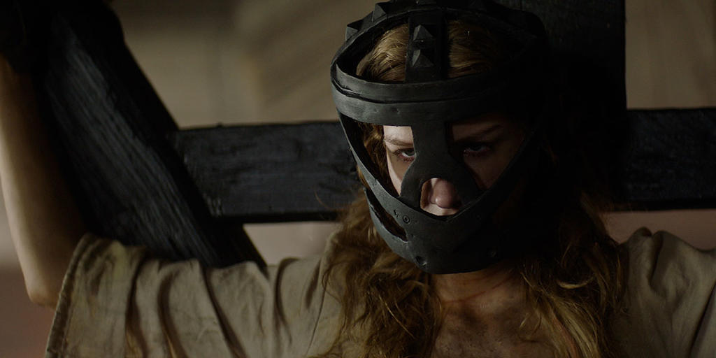 Grace (Charlotte Kirk) bound to a cross, with an iron mask that muzzles her.