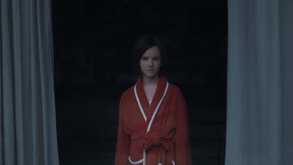 Ellie (Lena Watson) in a bathrobe, looking out a window.