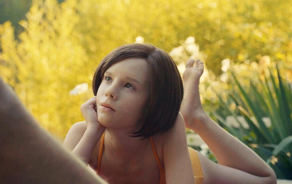 Ellie (Lena Watson) lying in the grass in a bathing suit.