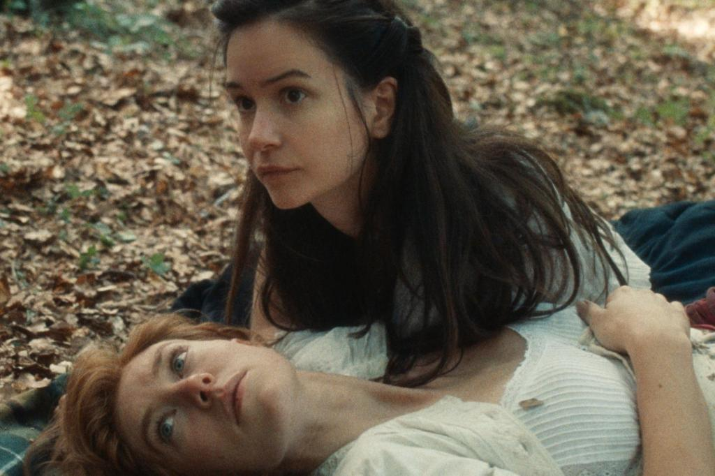Abigail (Katherine Waterston) and Tallie (Vanessa Kirby) cuddling in the forest.