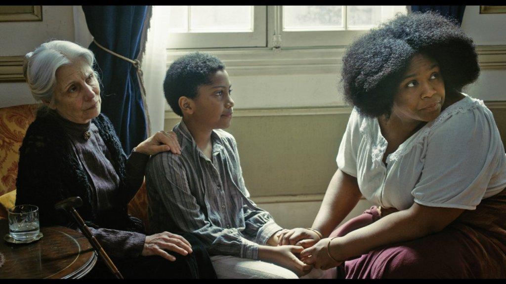 Isabel (Thaia Perez) sitting behind João (Agyei Augusto) as Iná (Mawusi Tulani) holds his hands.