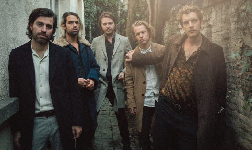 The band Balthazar, consisting of five white guys, standing in a narrow back alley.