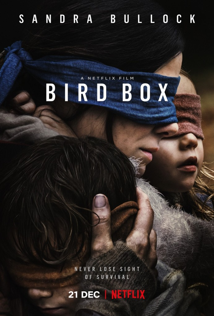 The film poster showing Malorie (Sandra Bullock) with blindfolded eyes, cradling both her children who are also blindfolded.