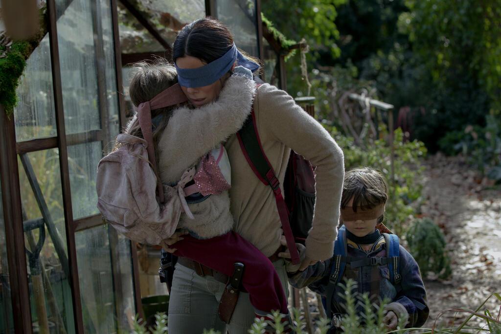 Blindfolded, Malorie (Sandra Bullock) carries her daughter Girl (Vivien Lyra Blair) and holds her son Boy's (Julian Edwards) hand. The children are blindfolded as well.