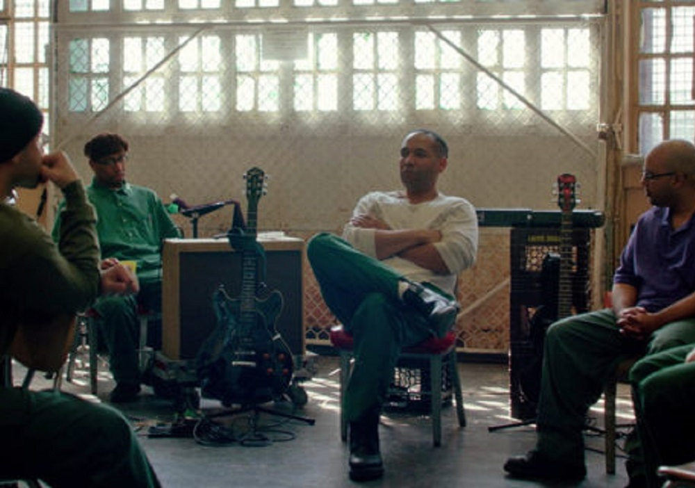 A group of men sitting in a circle surrounded by instruments.