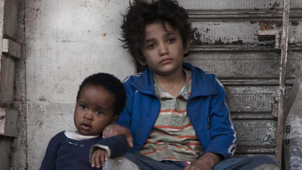 Zain (Zain Al Rafeea) and Yonas (Boluwatife Treasure Bankole) sitting next to each other, looking sad and tired.