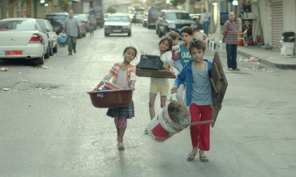 Zain (Zain Al Rafeea) leading a group of children, all carrying building supplies.