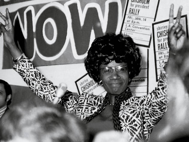 Shirley Chisholm, her arms raised, making victory signs, looking at the camera.