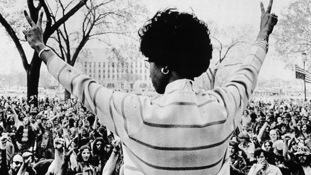 Shirley Chisholm, her arms raised, making victory signs, looking at a crowd, her back to the camera.