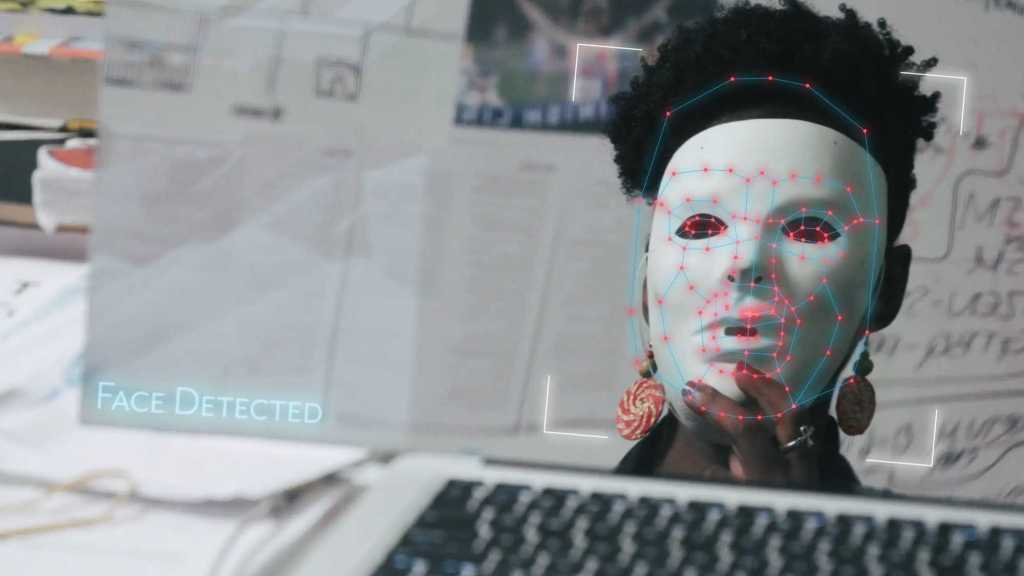 Joy Buolamwini tricking a face tracking software by wearing a white mask.