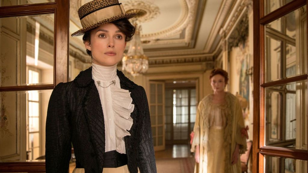 Colette (Keira Knightley) standing in a doorway, Georgie Raoul-Duval (Eleanor Tomlinosn) in the background.