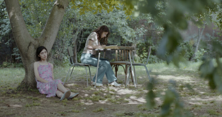 Teenaged Nana (Mariam Iremashvili) and Irina (Nina Mazodier) in the garden together.