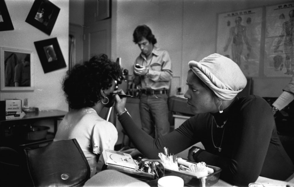 A Black woman marking another Black woman's ear with a pen.