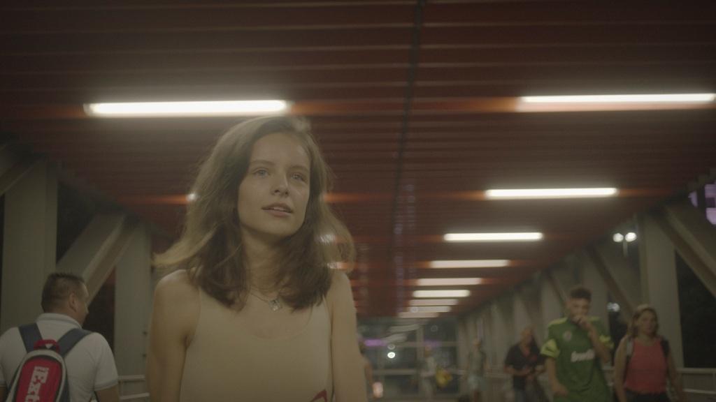 A young woman (Victoria Maranho) walking through a passage.