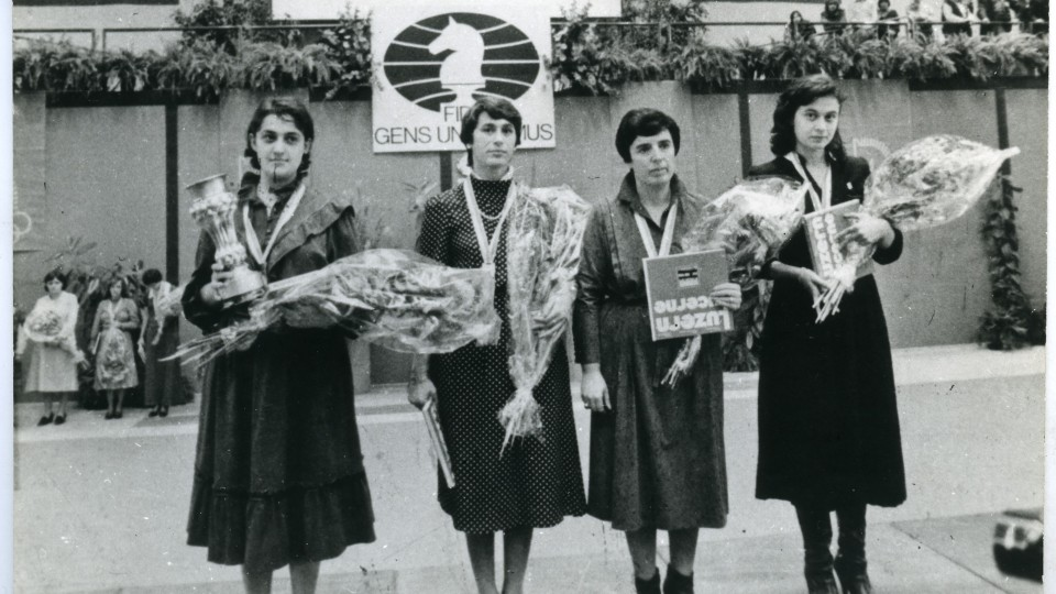 A historic picture of all four women holding flowers and trophies.