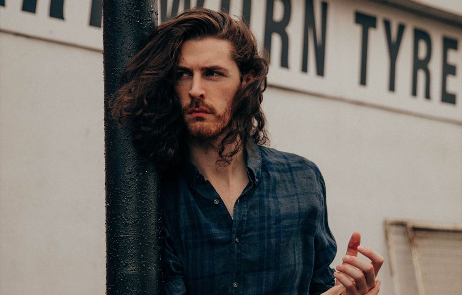 Hozier leaning against a lantern post